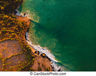 Aerial view of rocky shore with ocean waves and warm sunset.