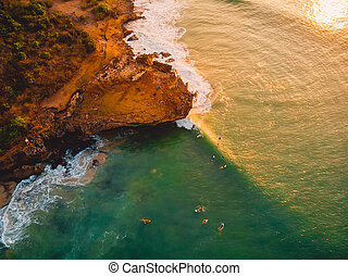 Aerial view of rocky shore with surfers, waves and warm sunset. Drone shot in Bali