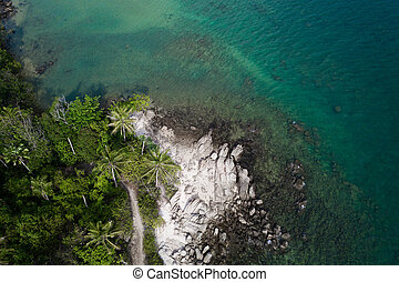 Aerial view of rocky shore with turquoise sea water and tropical green trees