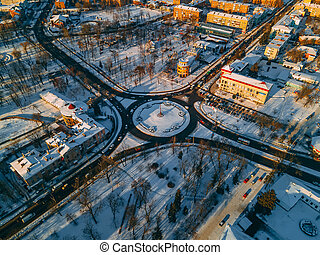 Aerial view of roundabout road with circular cars in small european city at winter sunset
