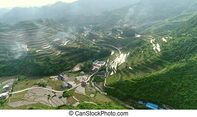 Aerial view of rural village surrounded by green terraced rice field farms in South of China