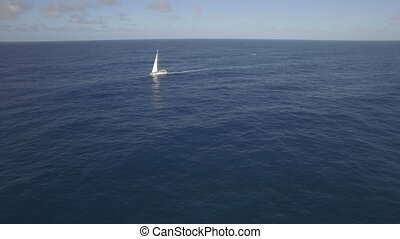 Aerial view of sailing white yacht in empty ocean blue water against clear sky, Mauritius Island