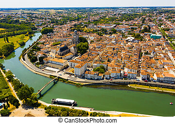 Aerial view of French town of Saintes on banks of Charente river overlooking medieval Roman Catholic cathedral on summer day..