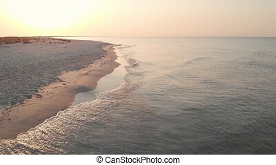 Aerial view of sandy beach and ocean with waves.