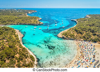 Aerial view of sandy beach, blue sea, people and yachts
