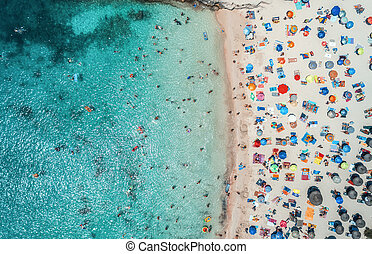 Aerial view of sandy beach with colorful umbrellas and blue sea