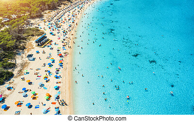 Aerial view of sandy beach with colorful umbrellas and sea
