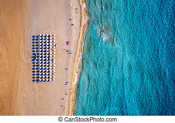 Aerial view of sandy beach with colorful umbrellas, swimming people in sea bay with transparent blue water at sunset in summer. Aerial top view on the beach, umbrellas, sand and sea waves.