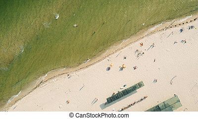Aerial view of sandy beach with tourists.