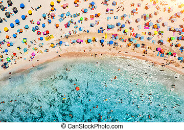 Aerial view of sandy beach with umbrellas and sea at sunset