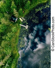 Aerial view of sauna house by the lake shore. Wooden pier with fishing boats.