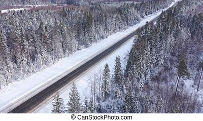 Aerial view of scenic landscape with straight road surrounded by snow covered woodland on winter day. High quality 4k footage