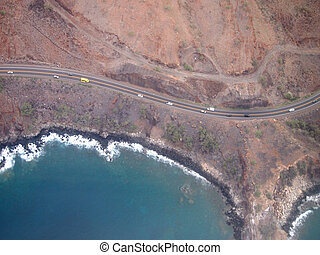 Aerial view of scenic road with cars driving along the coast of Maui, Hawaii and shallow waters during the day.
