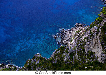 Aerial view of sea and rocky coast on sunny day.