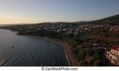 Aerial view of sea and shore with resort town at sunset,...