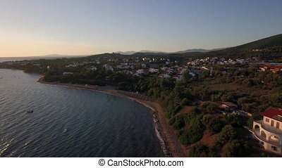 Aerial view of sea and shore with resort town at sunset, Greece
