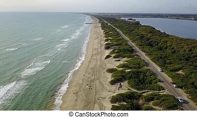 Aerial view of sea beach road trees and water areas under...