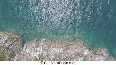 Aerial view of sea waves crashing on rocks of tropical island