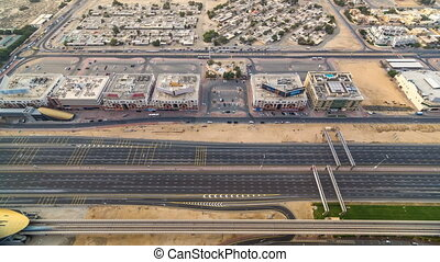 Aerial view of Sheikh Zayed highway road timelapse in Dubai with traffic and a metro station.