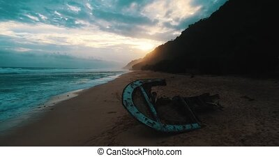Aerial view of shipwreck at the beach during amazing sunset