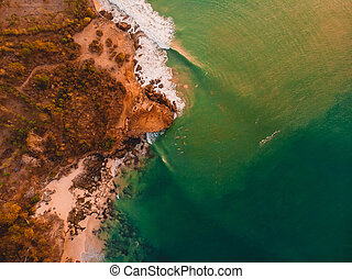 Aerial view of shore with ocean waves and sunset tones.