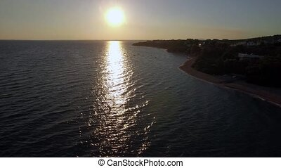 Aerial view of shoreline and sea with boats at sunset -...