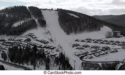 Aerial view of Ski Resort with Ski Slopes and Skiers. Snowy Fir Forest. Bukovel