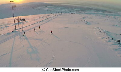 Aerial view of skiers and snowboarders at sunset