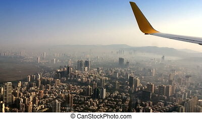 Aerial View of skyscrapers in a haze of the plane engine
