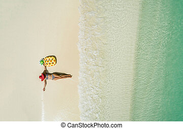 Aerial view of slim woman swimming on the transparent turquoise sea. Summer seascape with girl, beautiful waves, colorful water. Top view from drone