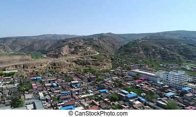 Aerial view of small poor town next the arid terraced farm ...
