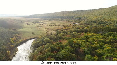Aerial view of small river with forests. Majestic landscape