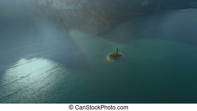 Aerial view of small rock on the lake