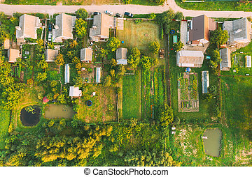 Aerial View Of Small Town Cityscape Skyline In Summer Day. Residential District, Houses And Garden Beds In Bird's-eye View