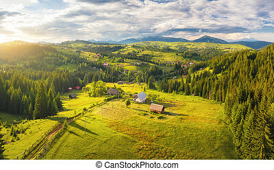 Aerial view of small village in Carpathian mountains at sunset