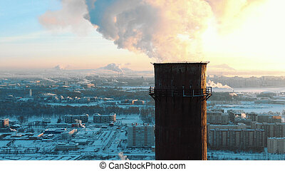 Aerial view of smoking chimneys in a residential area of the city at sunset in winter