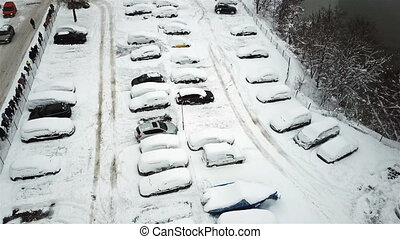 Aerial view of snow-covered cars stand in the parking lot on a winter day