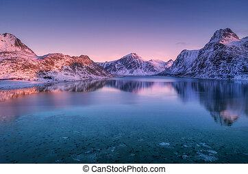 Aerial view of snow covered mountains and sea at colorful sunset