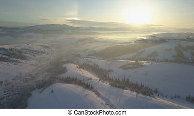 Aerial view of snow-covered mountains. Rural landscape in winter. Flight over a village in Carpathian mountains.