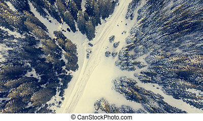 Aerial view of snow covered road through a forest.