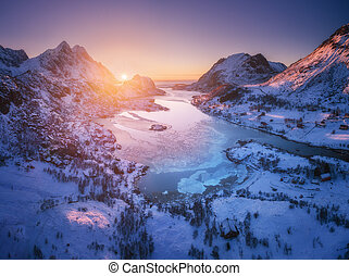 Aerial view of snowy mountains, sea, purple sky at sunset