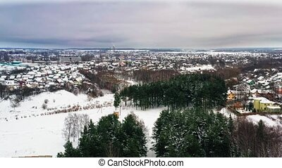 aerial view of snowy winter park. Pines and trees without...