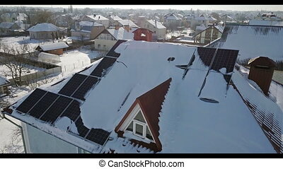Aerial view of solar panels on the roof of the house after a heavy snowfall in the winter. Renewable energy production modules