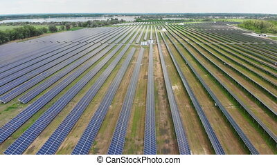 Aerial view of Solar Power Station. Field of Solar Panels Stands in a Row in the Fields for Power Production at Sunny day. Drone fly over Solar Farm. Renewable green energy and electrical technology