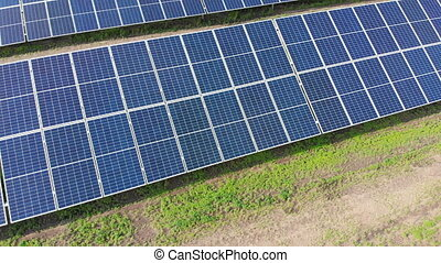 Aerial view of Solar Power Station. Solar Panels Stand in a Row on Green Field. Sunny day. Drone fly over Solar Farm. Renewable green energy technology. Alternative energy sources. Power Production.