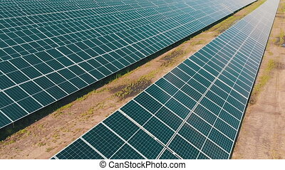 Solar Power Station in Green Field on Sunny day. Aerial view. Solar Panels Stands in a Row in Field for Power Production. Drone fly over Solar Farm. Renewable green energy. Alternative energy sources.