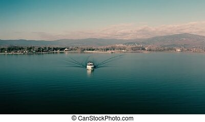 Aerial view of speeding motor boat and distant mountainous...