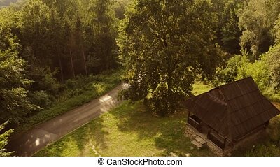 Aerial view of spooky ancient wooden cabin in a forest. Road...