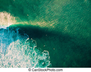 Aerial view of surfing at big waves. Surfers and ocean wave at sunset light
