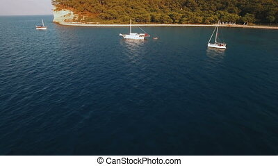 Aerial View of Swimming Ship in a Bay with Depp Blue Water. Sunset on Sea, Shot in 4K UHD